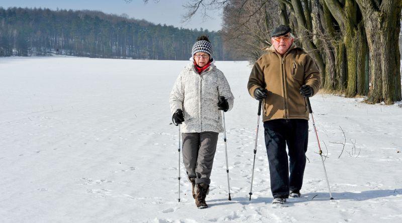 Altes Paar geht im Schnee Nordicwalken. Arthrose
