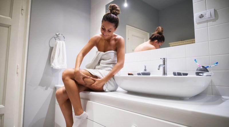 Frau überprüft ihre Oberschenkel auf Cellulite. Frau in weißem Bad. Cellulite Behandlung