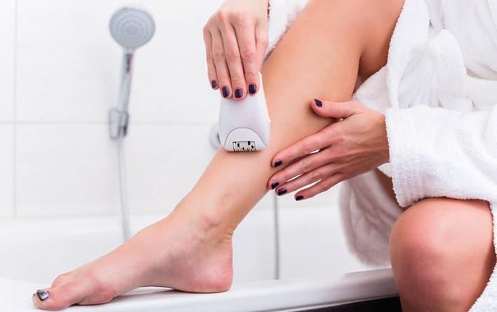 Frau entfernt mit Epiliergerät Haare am Bein. Haarentfernung