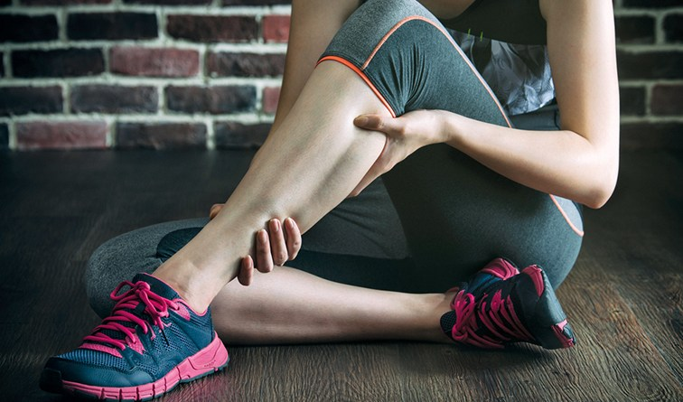 Frau mit Wandenkrampf. Frau in Sportkleidung hält sich die Wade. Magnesiumdefizit