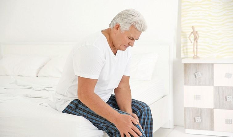 Älterer Mann sitzt am Bett und hält sich Knie vor Schmerzen. Entzündungen