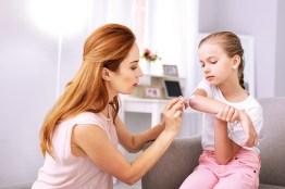 Mutter cremt Tochter mit Wundsalbe die Wunde ein. Wundversorgung