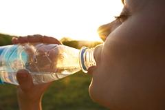 Frau Trinkt Wasser aus Flasche im Freien. volles Haar