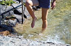 Frau kneippt in Fluss. leichte Beine