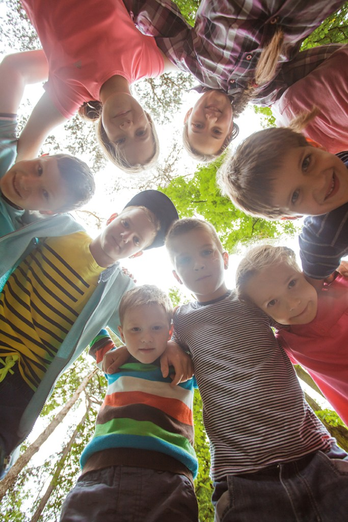 Viele Kinder stecken die Köpfe zusammen. Kopfläuse