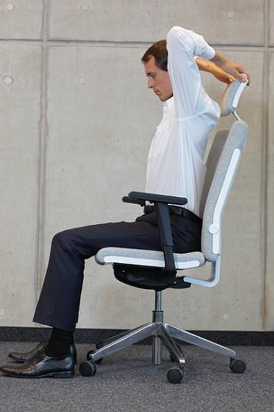 Mann auf Bürostuhl dehnt Wirbelsäule. Rückenschmerzen Übungen