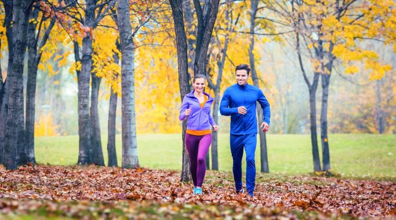 Pärchen joggt im Park im Herbst. Herbstlaub. Regeneration