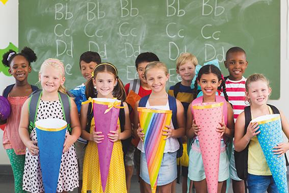 Gruppe Schüler vor Tafel mit Schultüten in der Hand. Fit für die Schule