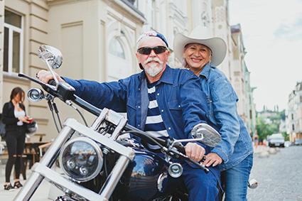 Altes Ehepaar auf Motorrad in Jeanskleidung. Vitalität im Alter