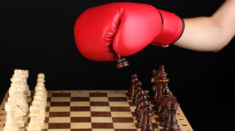 Hand mit rotem Boxhandschuh spielt Schach. Schachbrett. Aminosäuren aus der Apotheke