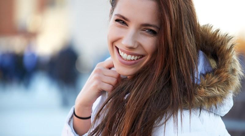 Lächelnde Frau draußen mit Winterjacke. Anti-Aging