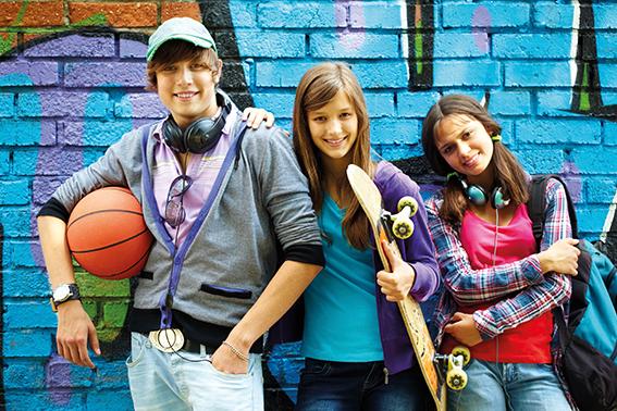 Gruppe von Jugendlichen vor Backsteinmauer. Graffi auf Mauer. Energydrinks Auswirkungen
