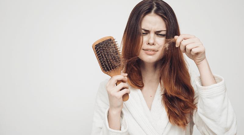 Frau verliert viele Haare. Haare in der Bürste. Frau ist unglücklich. Haarausfall verhindern