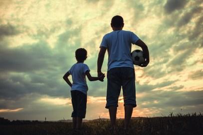 Vater und Sohn stehen mti Fußball in der Hand im Freien. aktiv werden