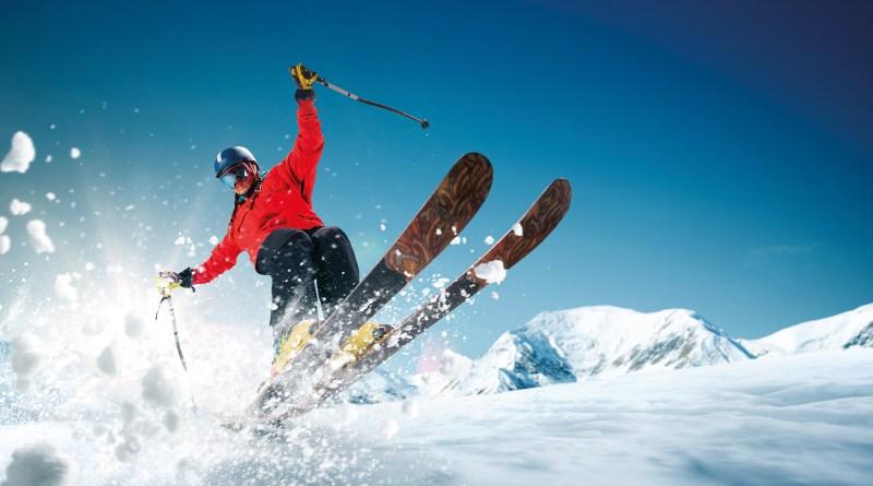 Mann auf Skiern von unten fotografiert. Schnee fliegt. Übungen fürs Skifahren Vorbereitung