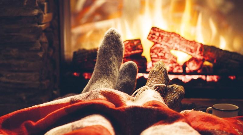 Füße verpackt in dicken Wollsocken und Decke vor Kamin. Feuer im Kamin. Kalte Füße. Kalte Füße Abhilfe