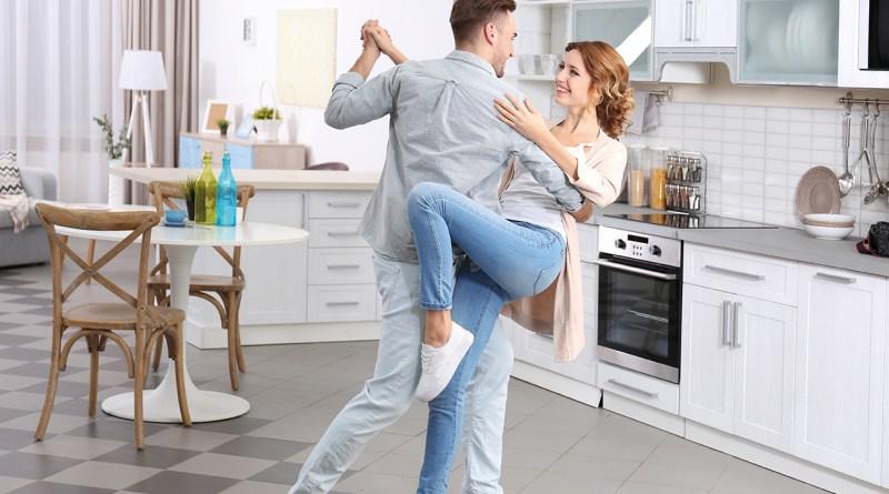Junges Paar tanzt in der Küche und ist glücklich. Schwungvoll aktiv werden