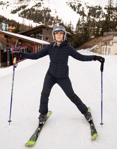 Frau macht Leisenübung auf Piste. Aufwärmübungen fürs Skifahren