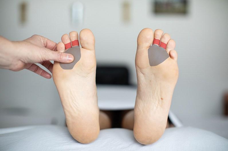 Füße einer Frau. Frau liegt. Fußreflexzonenmassage: Erkältungsszonen eingezeichnet