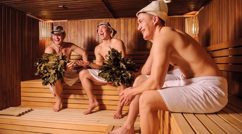 Drei Männer in Sauna. Saunahut. Birkenzweige. Finnische Sauna. Regeneration nach dem Sport