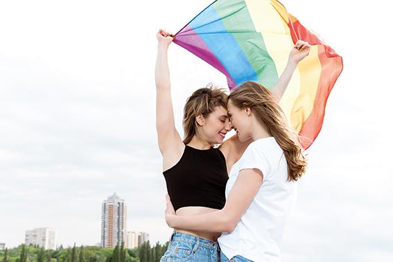 Zwei eng umschlungene Frauen im Freien mit Regenbogenfahne. LGBTQ Fahne. Bisexualität