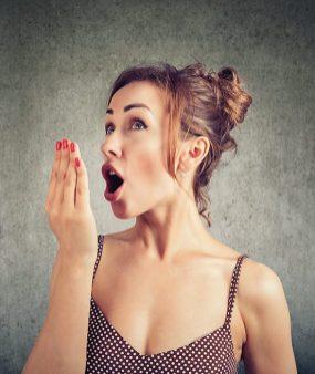 Frau hält sich Hand vor den Mund. Frau in Top. Frau haucht. Mundgeruch. innerer Frühjahrsputz