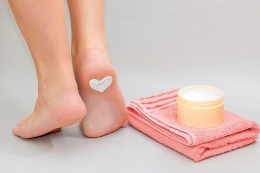 gepflete Füße. Herz aus Creme auf Ferse. Fußcreme