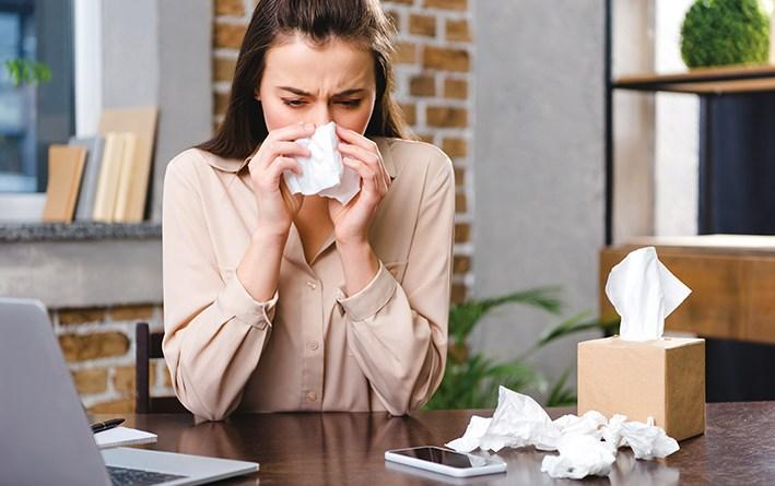 Frau, die sich in Büro schnäuzt. Allergie lindern