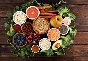 ballaststoffreiche Ernährung. Obst und Gemüse und Körner auf Holztisch. Hämorrhoiden loswerden