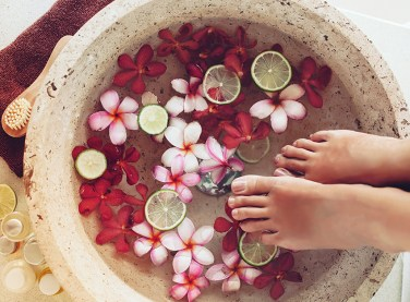 Füße in Fußbad. Fußbad aus Blüten und Zitrone. gepflete Füße