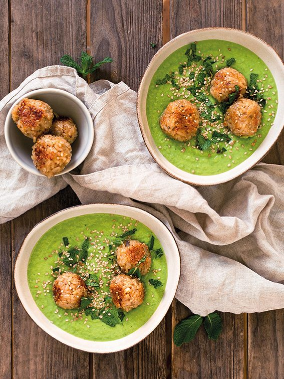 Erbsen-Minze-Suppe mit Reis-Sesam-Bällchen angerichtet in weißen Schüsseln auf Holztisch. Herbstgerichte