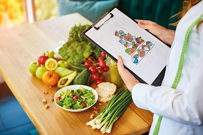 Obst und Gemüse auf Tisch. Frau hält Ernährungspyramide auf Clipboard. Durchfall