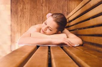 Frau liegt auf Handtuch in Sauna. Regenerieren nach dem Sport