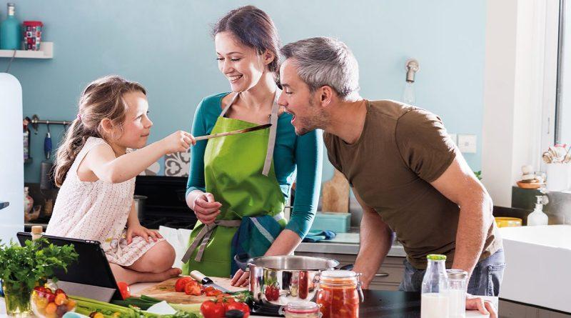Ein Löffel Vitamine. Kind füttert Vater mit Löffel. Glückliche Familie. Vitamine Fürs Immunsystem. Gesunde Familie. Obst und Gemüse am Tresen vor Familie