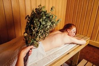 Frau liegt auf Bauch in Sauna. starke Abwehrkräfte. Birkenzweige