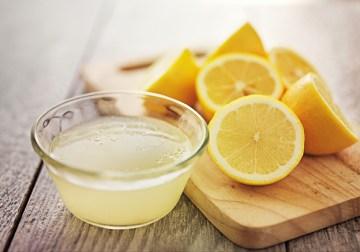 Frischgepresster Zitronensaft in kleiner Glasschüssel. Zitronen auf Holzbrett dekoriert. Handhygiene