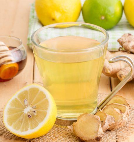 Zitronen-Ingwer-Tee angerichtet in Glas auf Holztisch. Starke Abwehrkräfte. Zitornen, Limetten und Ingwer dekoriert