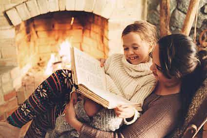 Mutter liest Tochter ein Buch vor vor dem Kamin. Winter. Starke Abwehrkärfte. Gemütllichkeit. Hygge.