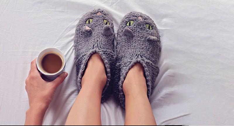 Frau mit Katzen-Socke und Tee im Bett. Kalte Füeß