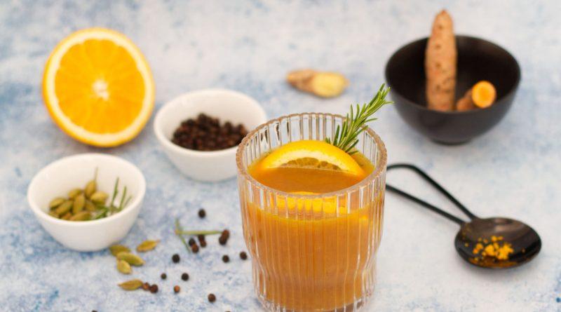 Spicy Orangen-Punsch angerichtet in Glas. Punsch Rezepte. Dekoriert mit Zutaten. Weihnachtspunsch aus weißem Untergrund