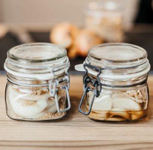 Zwiebel im Glas auf Holzbrett. Selbstgemachter Hustensaft mit Zwiebeln. Hausmittel gegen Husten