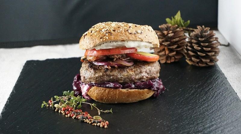 Wilder Löcker-Burger angerichtet auf schwarzer Schieferplatte. Schön dekoriert. Winterrezepte