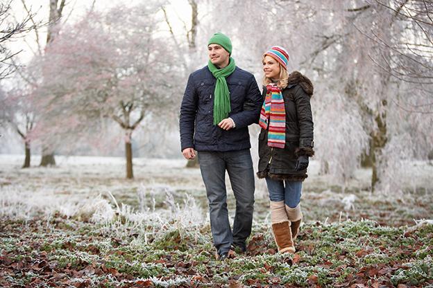Glückliches Paar sparziert auf Wiese. Winter, Herbst. Corona-Blues