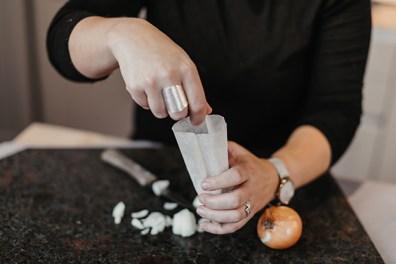 Frau füllt Zwiebel in Säckchen. Zwiebelsäckchen auf dunkler Steinplatte. Hausmittel gegen Schnupfen