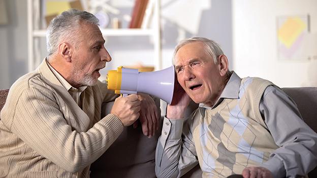 Senior spricht zu anderem Senior durch Megaphon. Schlecht hören. Pfropf im Ohr
