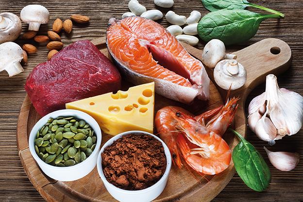 Zinkhaltige Lebensmittel. Fisch, Käse, Fleisch. Meeresfrüchte, Knoblauch etc auf Holztisch. Tipps für das Immunsystem