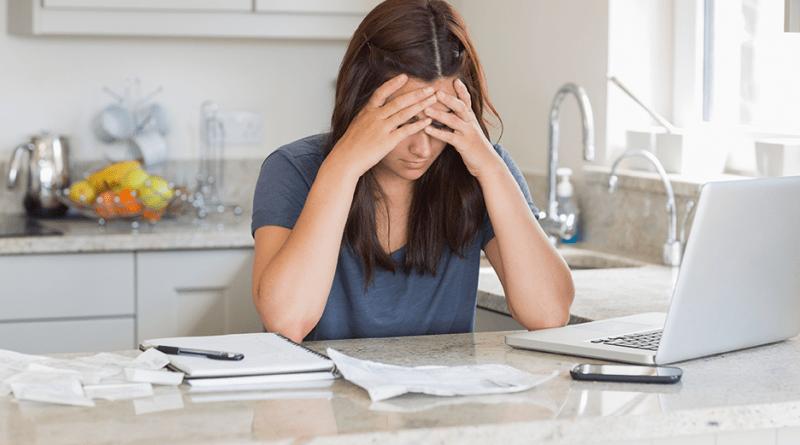 Gestresste Frau am Schreibtisch in Küche. Homeoffice. negative Stressoren