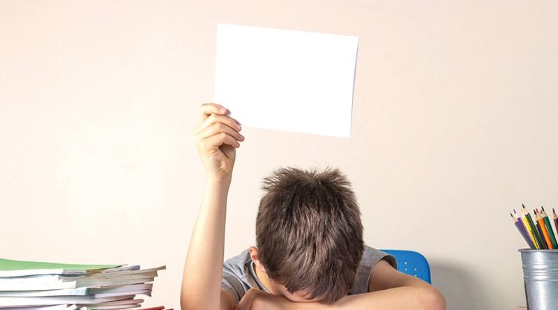 trauriger, frustrierter Bub, der den Kopf zwischen Büchern und Heften vergräbt. Corona und unsere Kinder