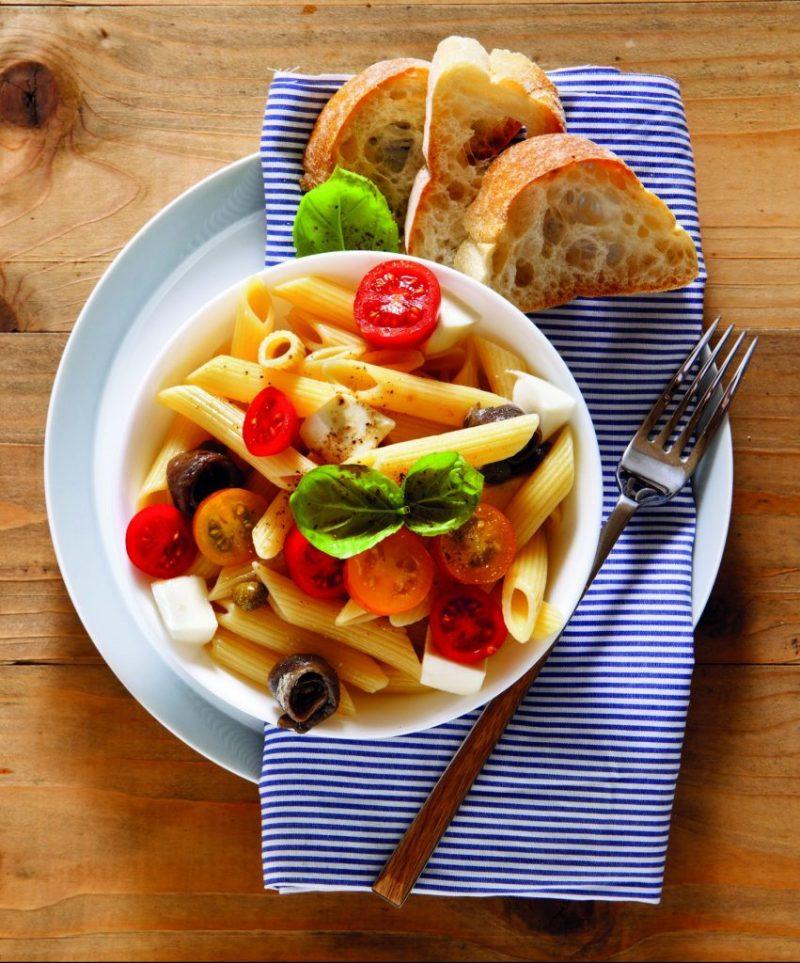 Kalter Thunfisch-Nudelsalat angerichtet in weißer Schüssel mit Ciabatta und Geschirrtuch schön dekoriert. Sommerrezepte