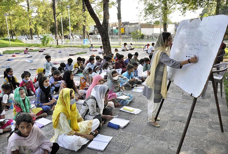 ISLAMABAD: August 26 – A volunteer teacher teaching the students in a local park in F-6 as educational institutes will be open from September 15 across the country after Covid-19 pandemic. APP photo by Saadia Haidari
